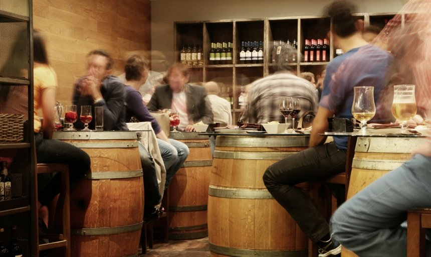Hazy view of a drinking area with people sitting on barrels and drinking alcohol