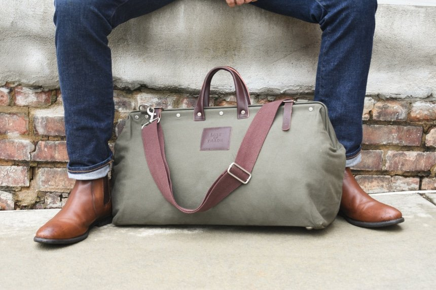Bespoke Post Weekender Bag Outside Sitting At Feet of Model Wearing Jeans and Boots Close Up