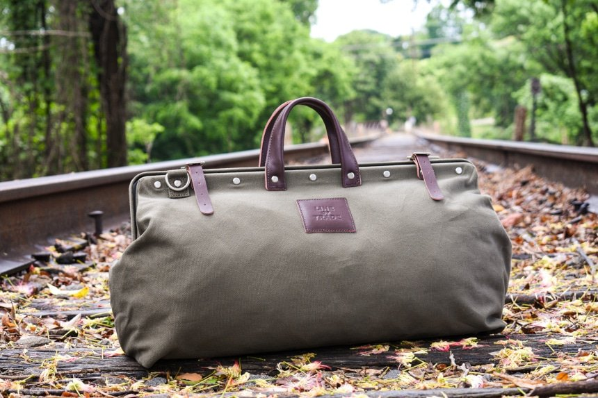 Bespoke Post Weekender Bag Outside on Railroad Sitting Up