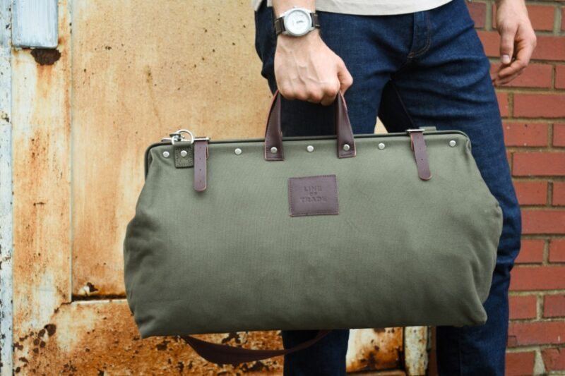 Male Model Holding Bespoke Post Weekender Bag Outside While Wearing Watch and Jeans