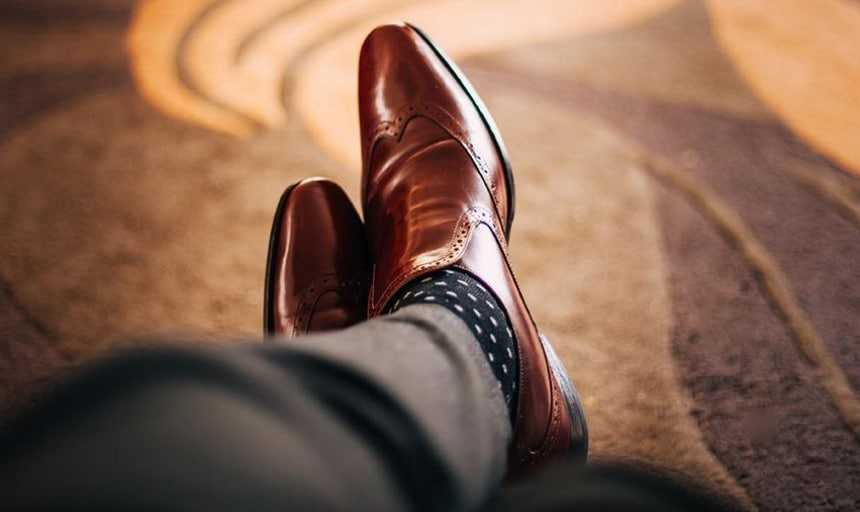 View from above of brown leather dress shoes and polka dot socks