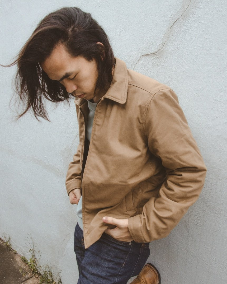 Male model leaning against a wall wearing Everlane Midweight Canvas Jacket, Fleece Crew, and Skinny Fit Jean