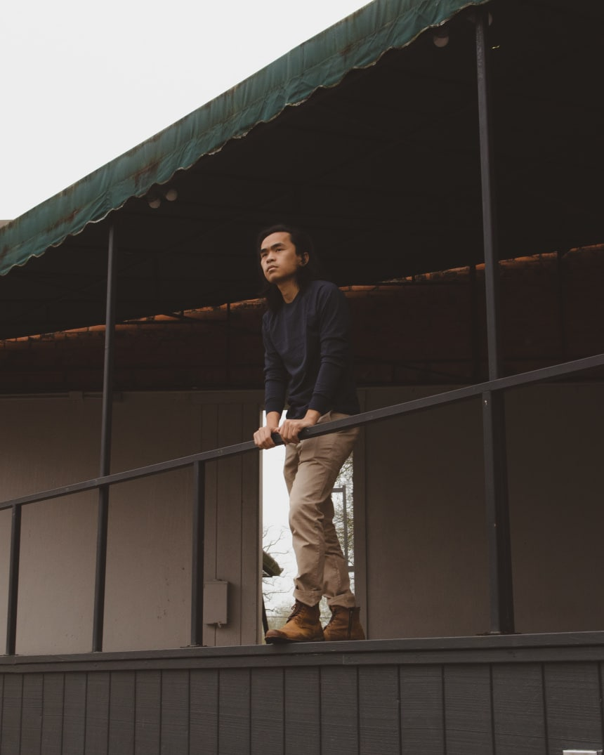 Model wearing Everlane heavyweight long sleeve tee and midweight slim chino and standing outside
