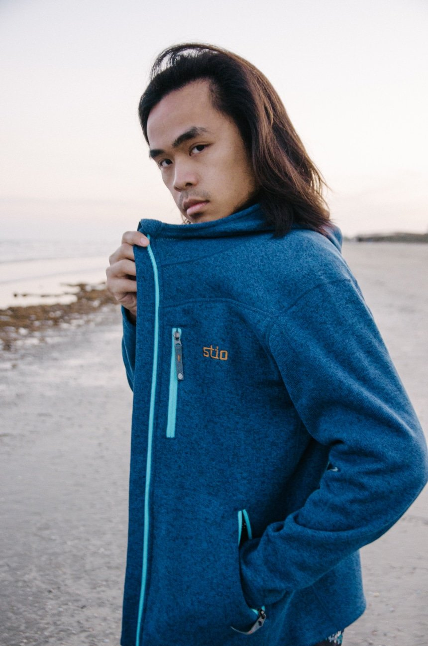 Close Up On Logo Of Model Wearing Stio Wilcox Fleece Hoodie and Looking In Camera At The Beach