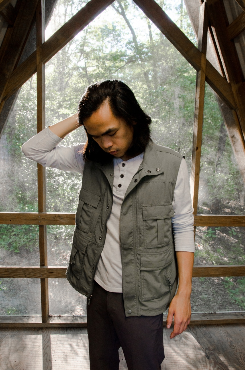Male Model Wearing TravelSmith Voyager 15-Pocket Vest in Olive Inside of Cabin in Park And Looking Down