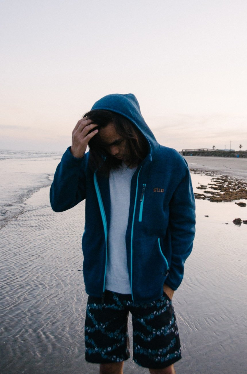 Model Wearing Stio Wilcox Fleece Hoodie and CFS Board Shorts While Holding Hood at the Beach While Looking Down