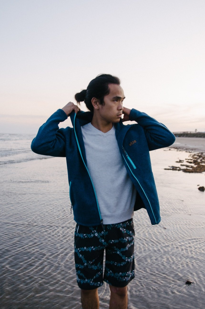 Model Wearing Stio Wilcox Fleece Hoodie and CFS Board Shorts While Holding Hood at the Beach While Looking In The Distance