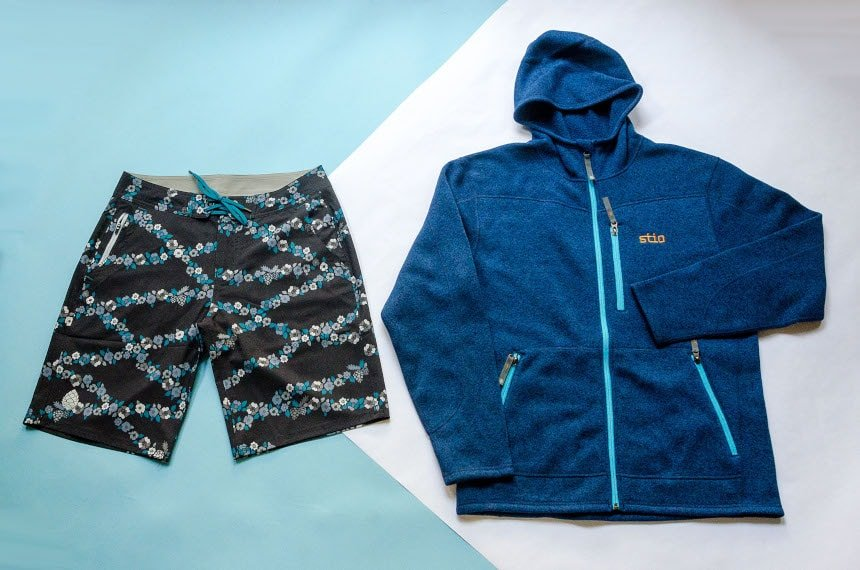 Stio CFS Board Short and Wilcox Fleece Hoodie on Blue and White Paper Backdrop Product Shots