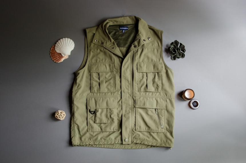 TravelSmith Voyager 15-Pocket Vest in Olive Sitting on Grey Background with Shells around