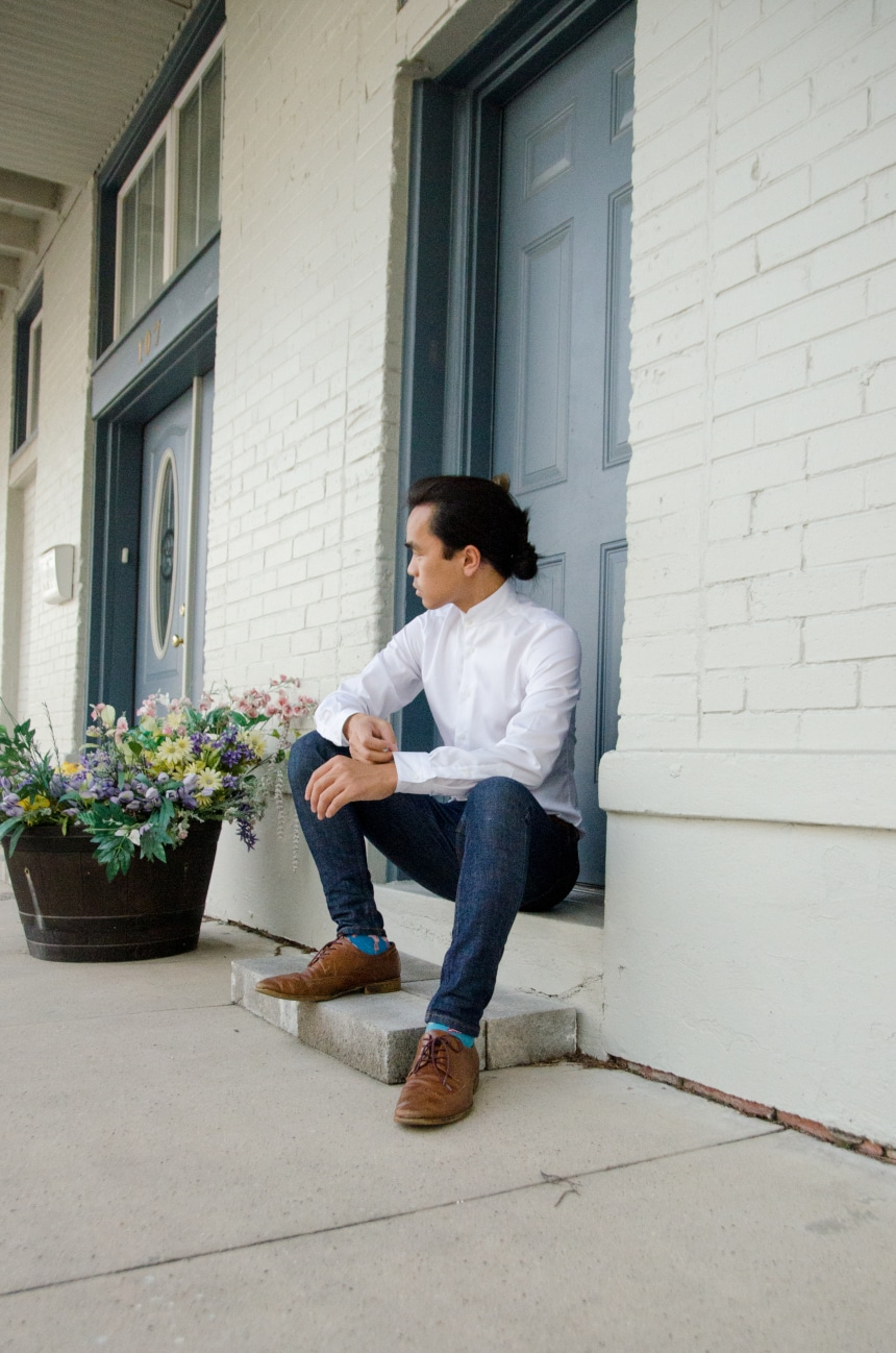 Model Wearing Apposta Coolmax Twill and Sitting On Stoop Wearing Jeans and Boots And Looking In The Distance