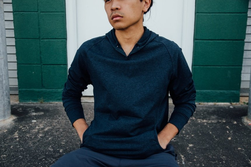 Model Wearing Public Rec Politan Hoodie And Sitting Down With Hands In Pockets