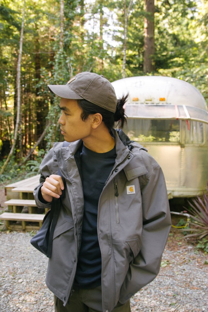 Man in woods holding backpack looking down wearing Carhartt Odessa Cap Rugged Flex Rigby Dungaree and Force Delmont Tee Looking to the Right