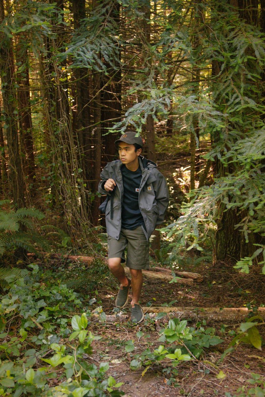 Man hiking through woods and carrying backpack wearing Carhartt Odessa Cap Rugged Flex Rigby Cargo Shorts Force Delmont Tee and Shoreline Jacket a
