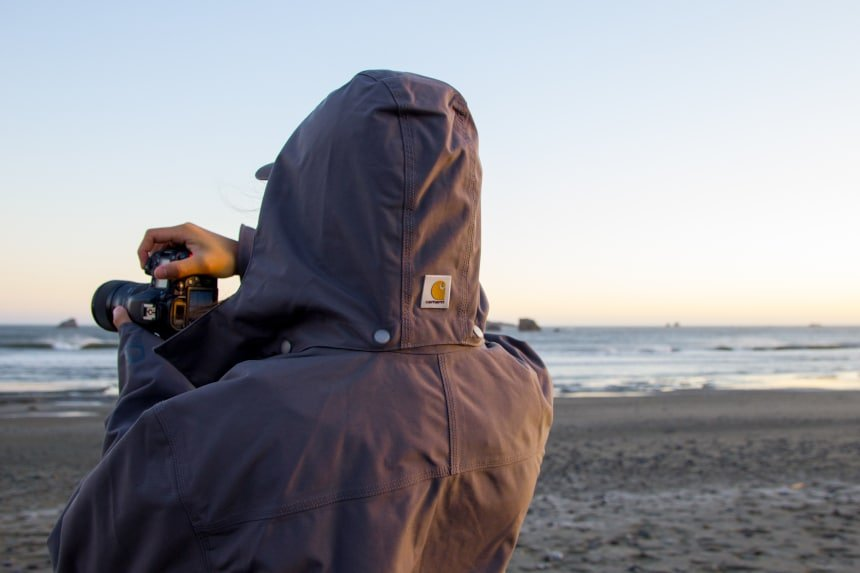Man-holding-camera-and-taking-photos-while-wearing-Carhartt-Shoreline-Jacket-at-the-ocean wider shot