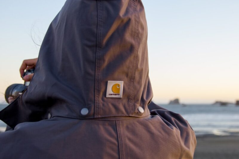Man holding camera and taking photos while wearing Carhartt Shoreline Jacket at the ocean