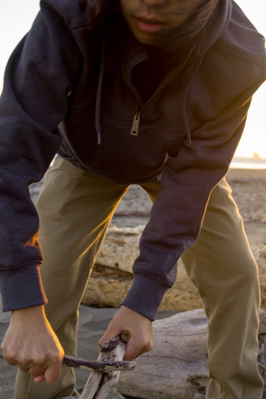 Man on beach trying to start fire with driftwood while wearing Carhartt Shoreline Jacket and Rugged Flex Rigby Dungaree