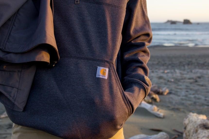 Man on beach wearing Carhartt Rain Defender Paxton Zip Mock Sweatshiert focusing on front pocket
