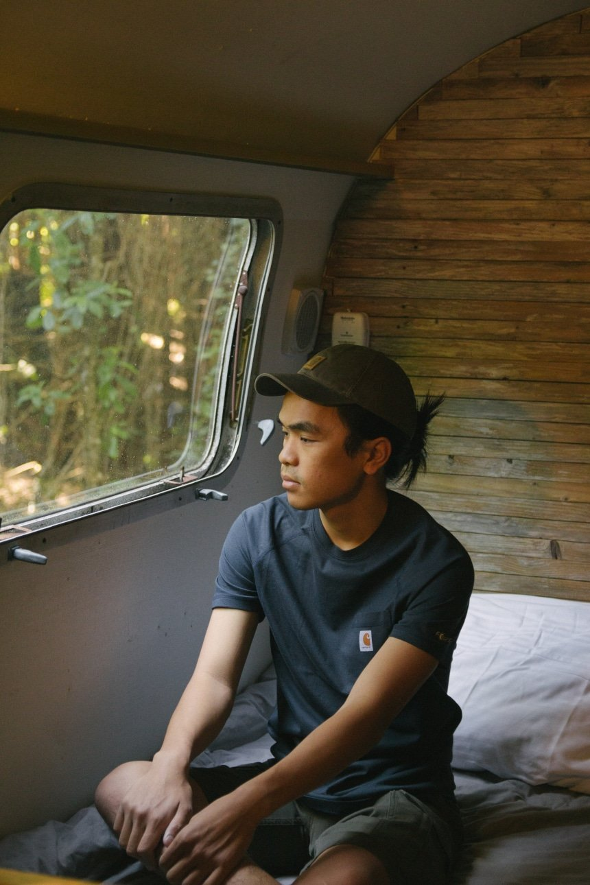 Man sitting in Airstream camper on bed looking out the window wearing Carhartt Odessa Cap Force Delmont Tee and Rugged Flex Cargo Shorts a