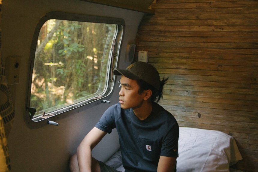 Man sitting in Airstream camper on bed looking out the window wearing Carhartt Odessa Cap Force Delmont Tee and Rugged Flex Cargo Shorts b