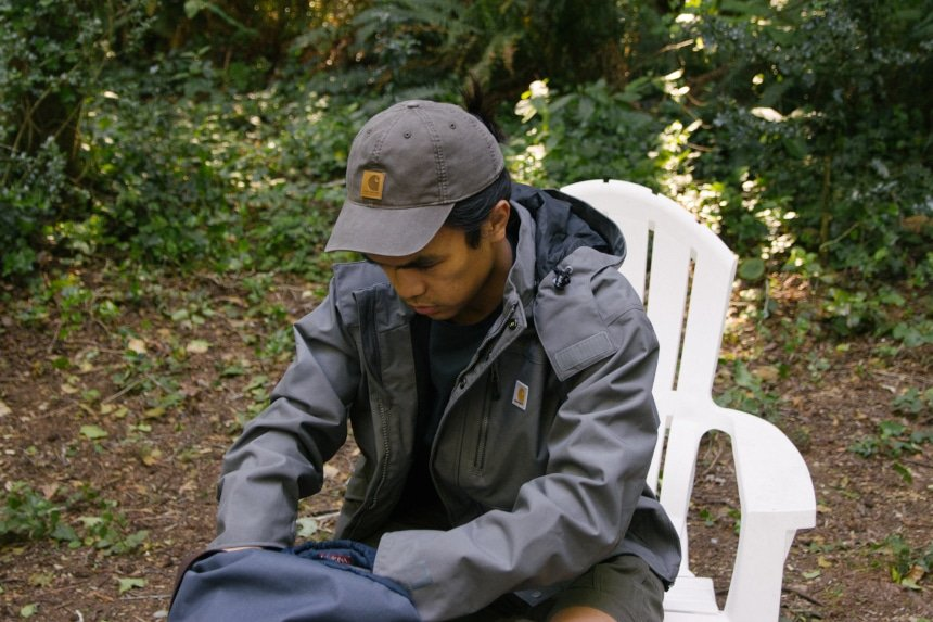Man sitting on chair looking through backpack while wearing Carhartt Shoreline Jacket Odessa Cap and Rugged Flex Rigby Dungaree