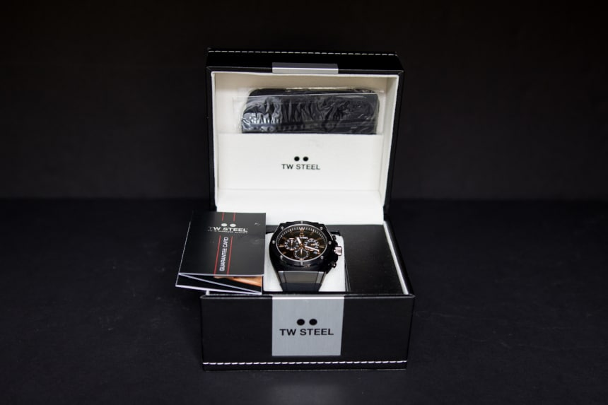 TW Steel CEO Tech front facing open leather watch box with watch and booklet inside on black background c