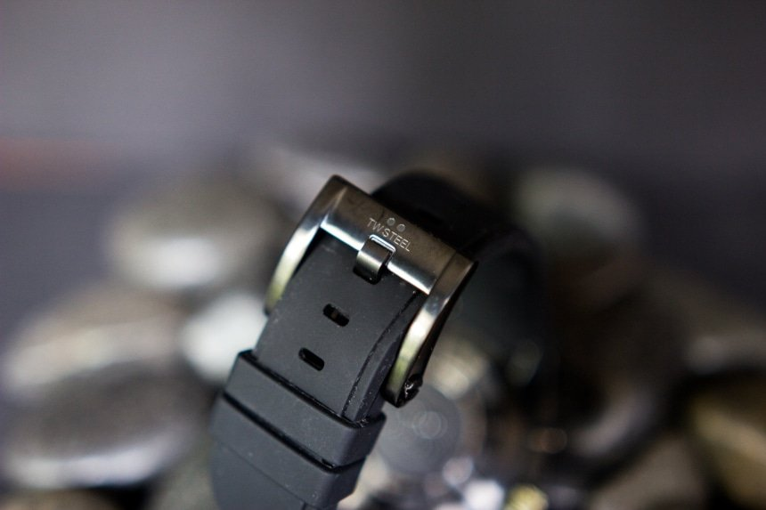 TW Steel CEO Tech watch band and clasp with logo back facing propped on top of black stones on black background a
