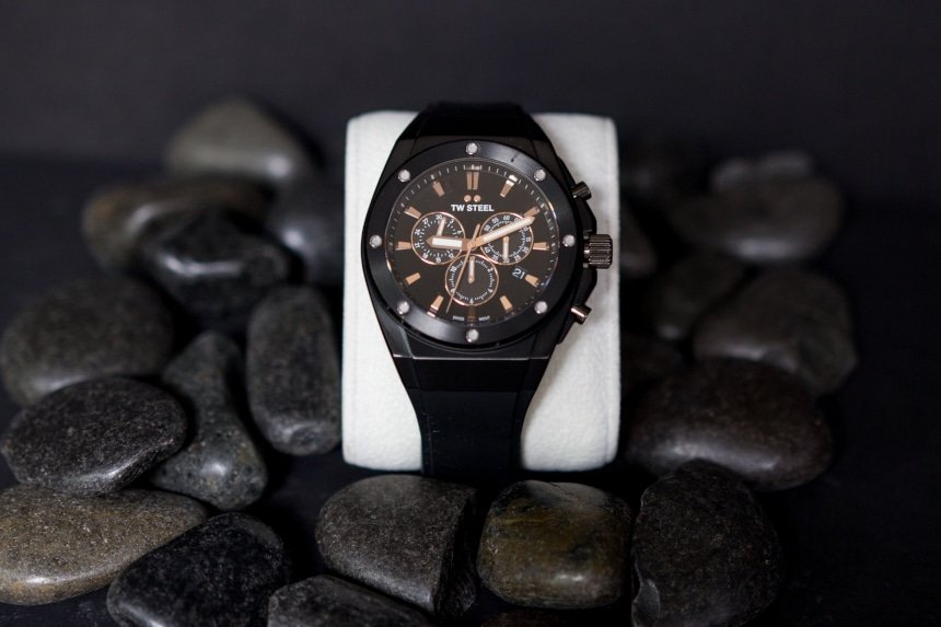 TW Steel CEO Tech watch propped up against black stones on black background a