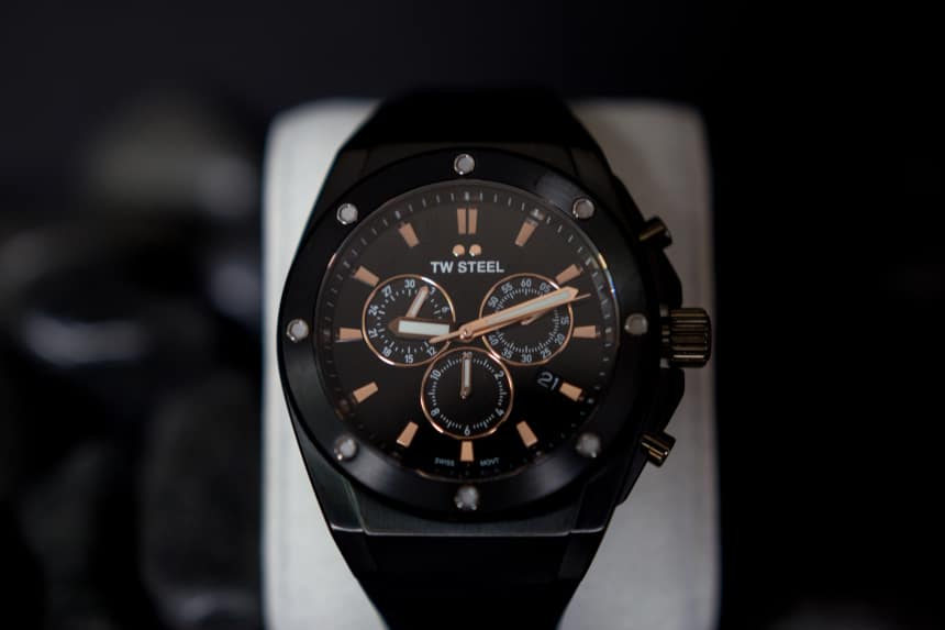 TW Steel CEO Tech watch propped up against black stones on black background c