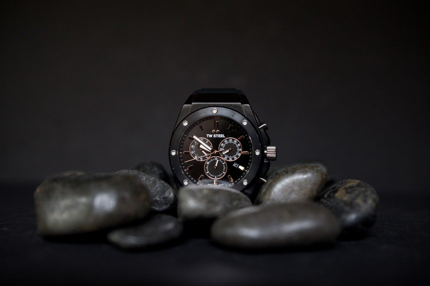 TW Steel CEO Tech watch propped up against black stones on black background f