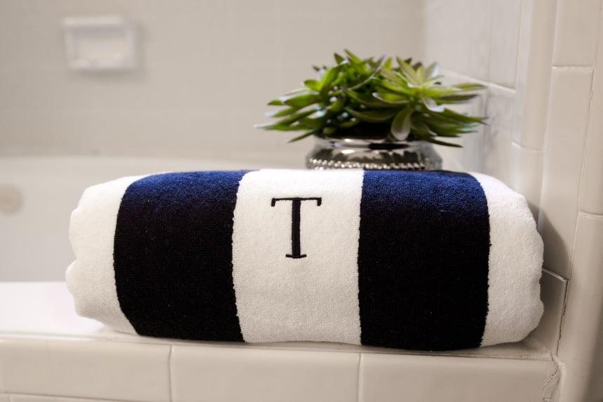 Luxor Linens Anatalya Egyptian Cotton Resort Beach Towel next to bath folded