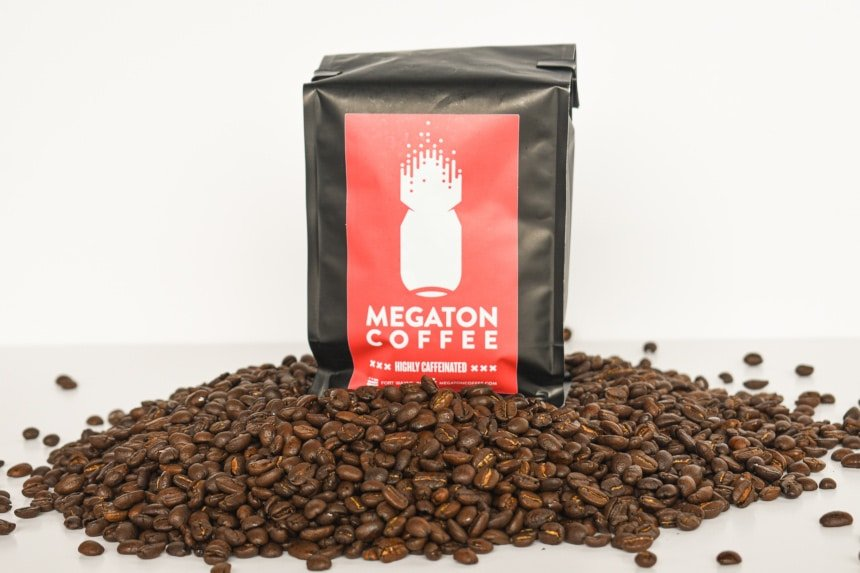 Megaton Coffee Packet Front Open with Beans in Foreground on White Background