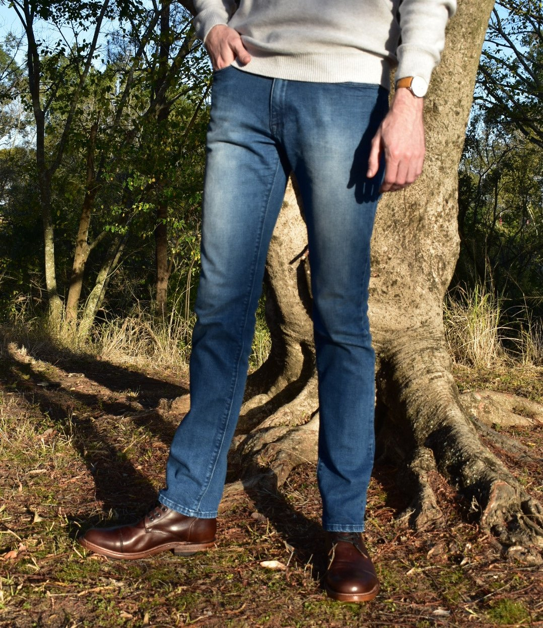 Model Wearing Mott & Bow Slim Laight Jeans with Liam Sweater Standing Up and Standing Next to Tree With Hand in Pocket and with White Sneakers - Torso Shot