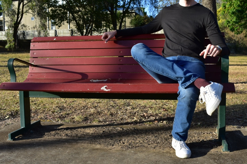 Model Wearing Mott & Bow Slim Laight Jeans with Slim Crew Long Sleeve Driggs Tee in Black, with Legs Crossed on Bench - Right Aligned