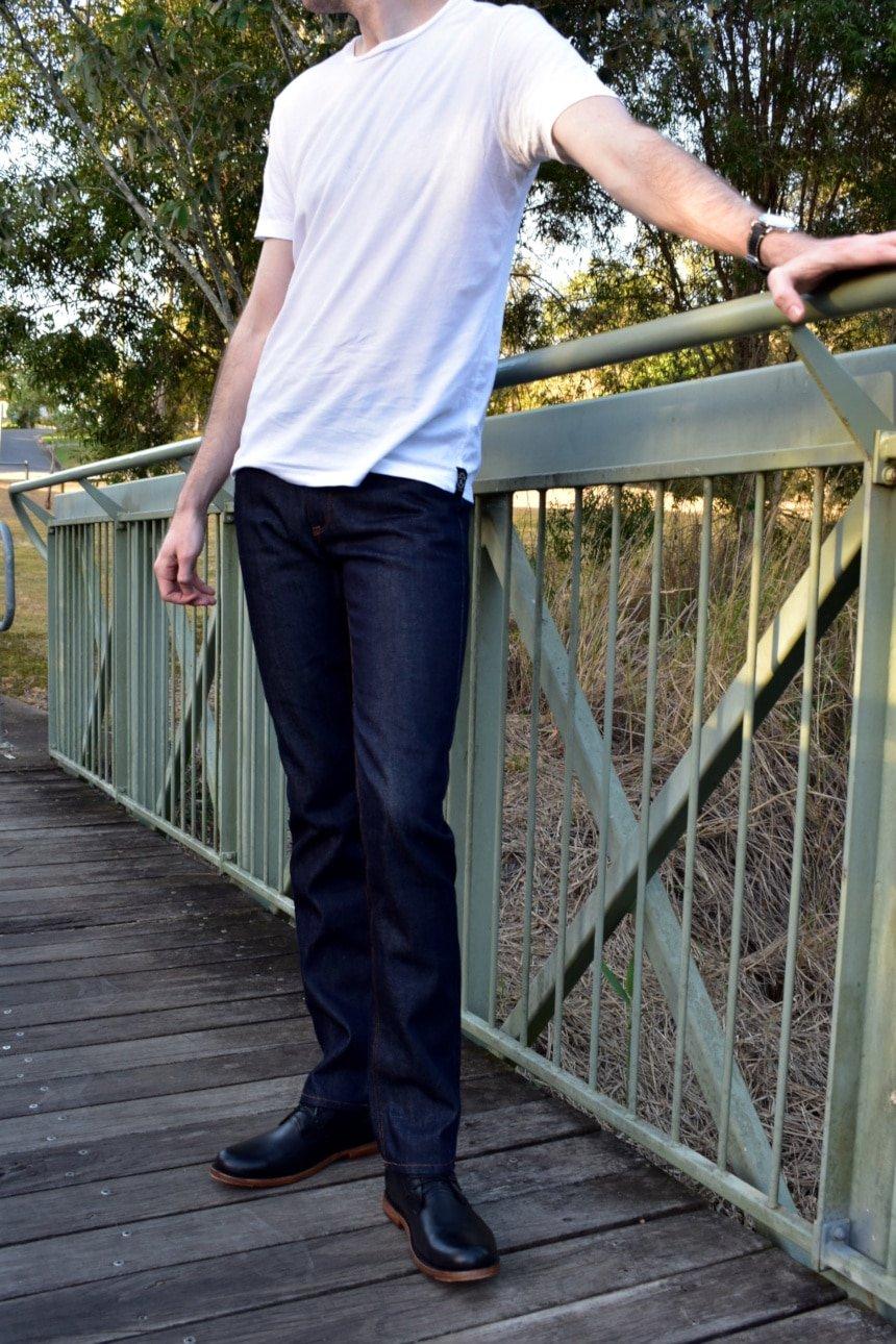 Model Wearing Mott & Bow Slim Nofolk Raw Jean with White Shirt Standing on Bridge