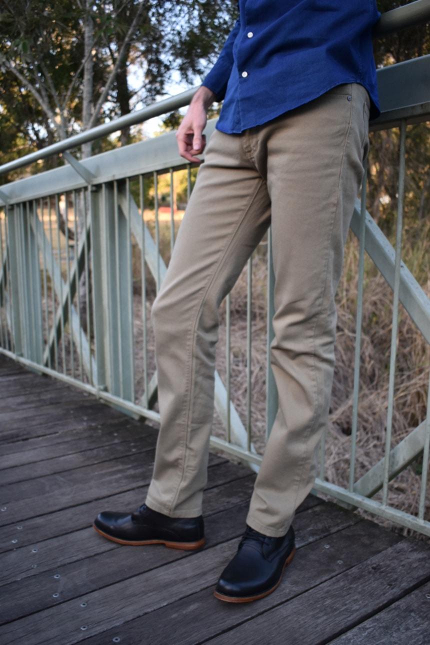 Model Wearing Mott and Bow Slim Mercer in Olive Close up of Denim against bridge
