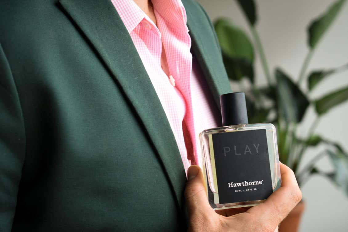 Male Model Wearing Charcoal Suit With Pink Shirt And Holding Hawthorne Play Fragrance Side Angle