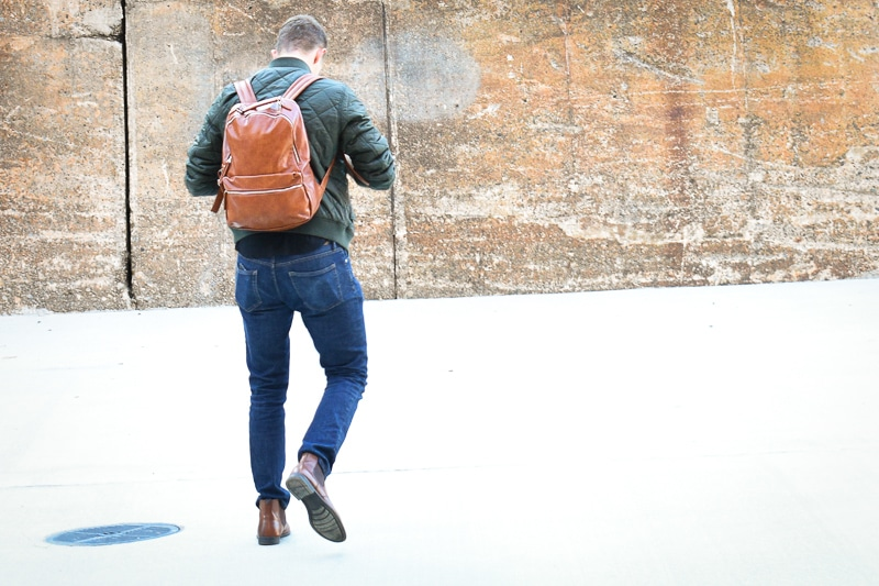 modern made man leather backpack walking away