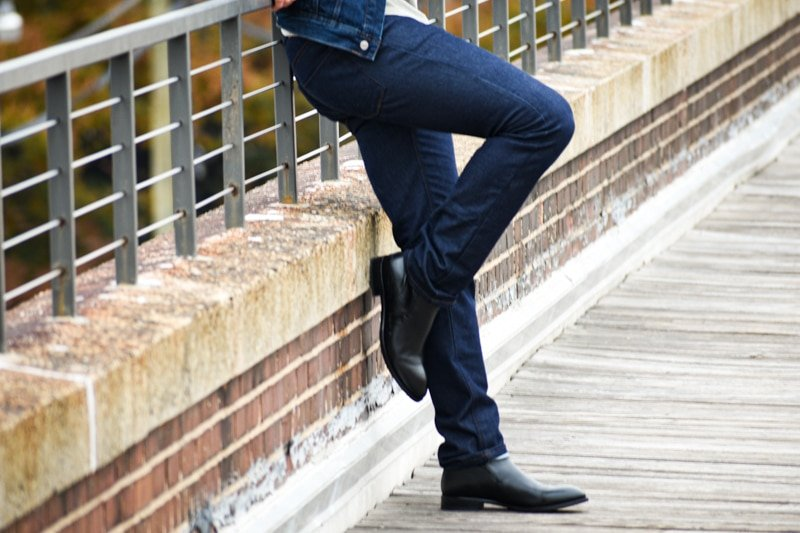 Best Jeans for Men Model Outside Leaning Against Guard Rail Wearing Slim Fit Dark Wash Jeans and Black Boots