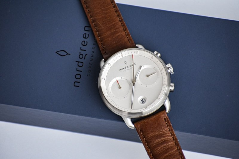 White dial pioneer against blue packaging