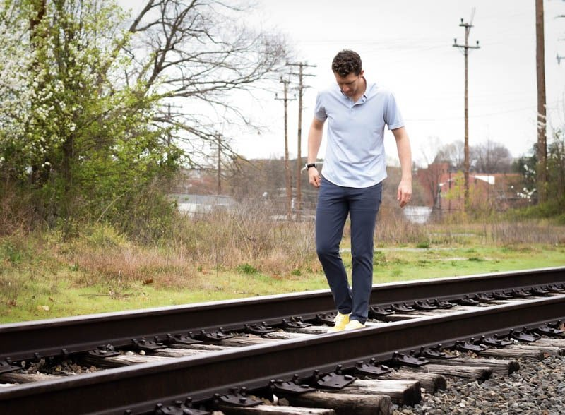 model walking down train tracks wearing western rise limitess shirt and diversion pants