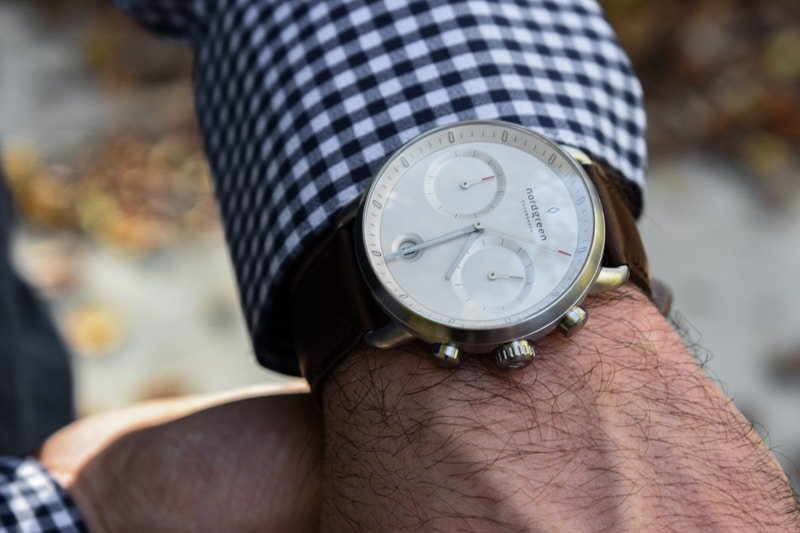 model wearing nordgreen pioneer white dial against blue checkered shirt