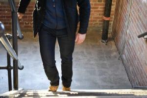 model walking up steps mott and bow jeans blue vest and black coat backlit
