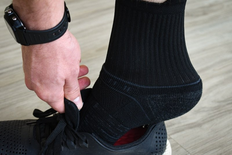 model putting on shoe wearing black strideline mid sock
