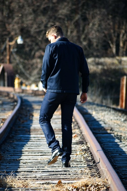model walking down train tracks dark blue jeans and black boots