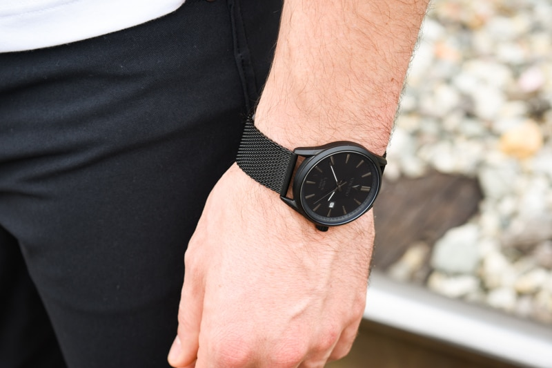 Vincero Kairos black strap black dial on wrist with model wearing jeans