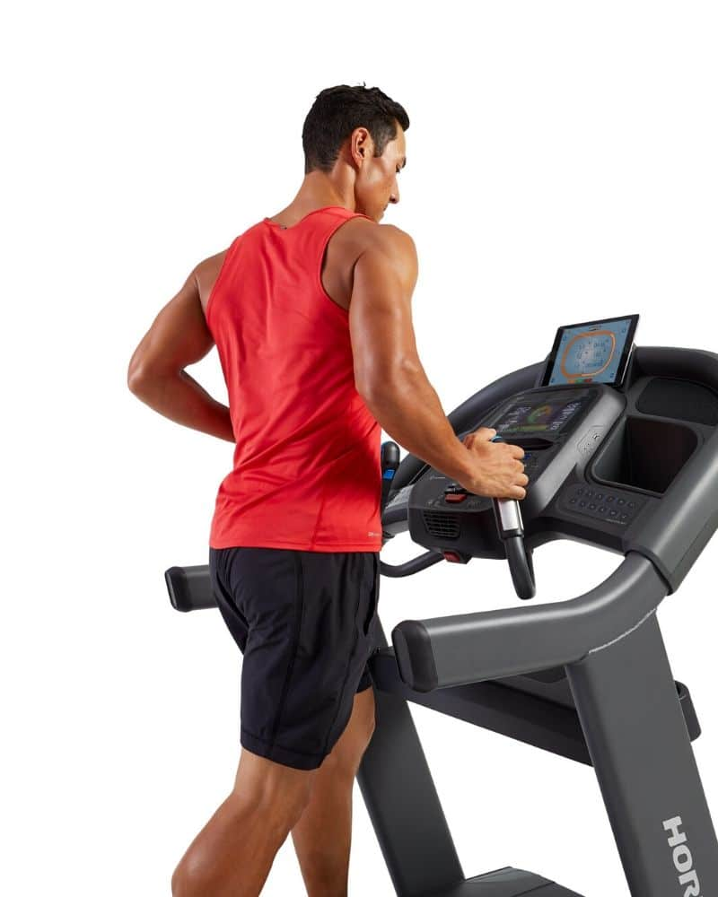 man in red shirt using heart rate feature treadmill