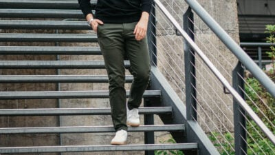 Best Chinos for Men Model Wearing Olive Asket Chinos Walking Down Stairs in White Sneakers