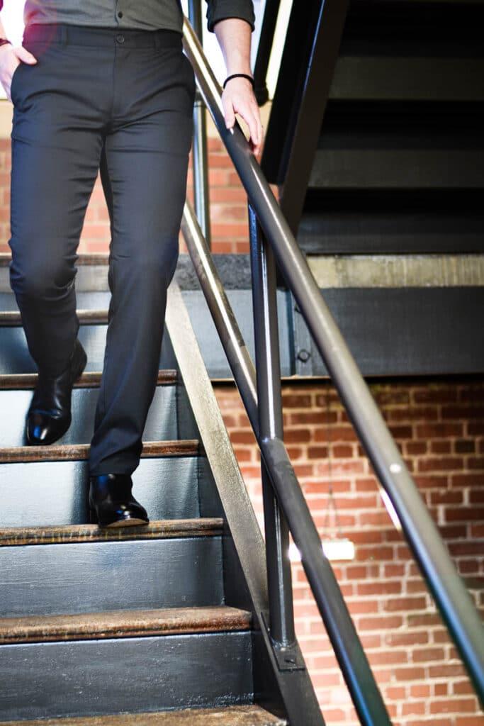 Black Mizzen Main Performance Chino on Model Walking Down Stairs