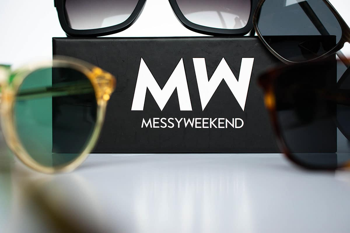 black messyweekend sunglasses case with several pairs around on white background