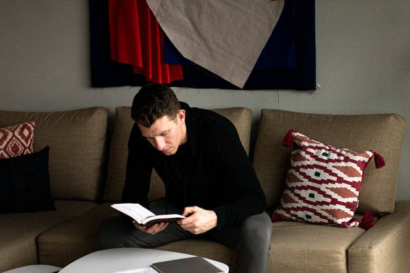 model wearing black hoodie reading book
